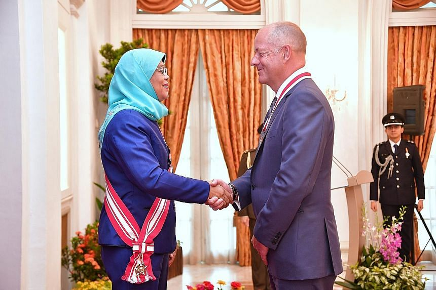 Pharmaceutical giant GlaxoSmithKline's former chief executive, Sir Andrew Witty, was conferred the Honorary Citizen Award by President Halimah Yacob at the Istana yesterday.