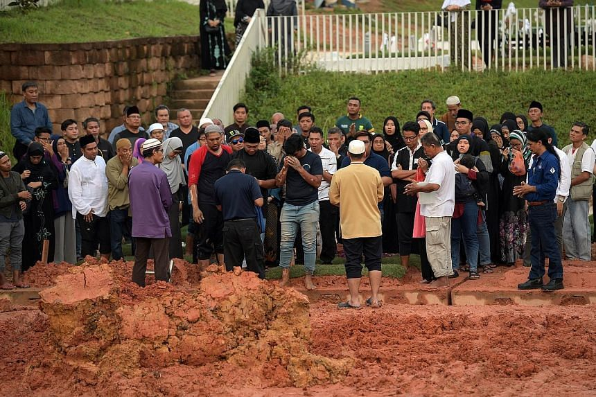 Madam Zarimah Mohamad's burial at the Choa Chu Kang Muslim Cemetery yesterday. Her eldest son said she had Stage 3 breast cancer about five years ago. She had surgery and chemotherapy, and had been feeling unwell since, but chose to continue working