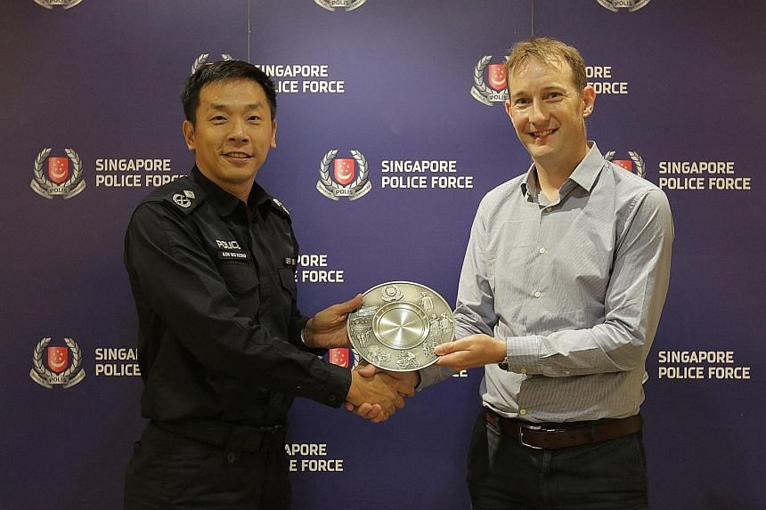 Assistant Commissioner of Police Koh Wei Keong, at the Public Transport Security Command, presenting the Public Spiritedness Award to Mr Keith Goldfinch, who was being honoured for helping the police to nab an upskirt video suspect in Newton MRT stat