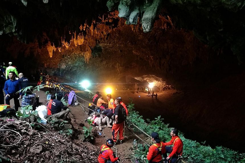 Thai rescue workers and park officials outside the Tham Luang Nang Non cave where 12 football players and their coach have been trapped since last Saturday.
