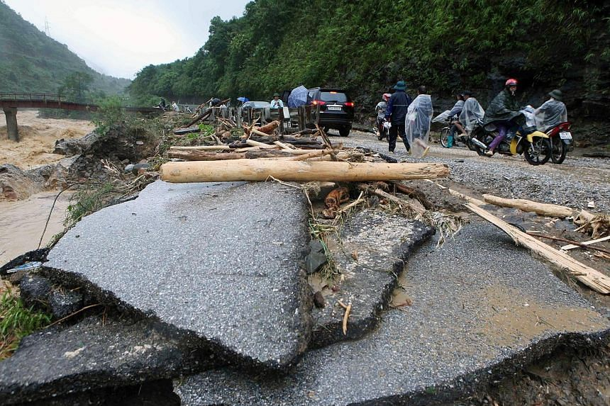 A flood-damaged road in Lai Chau province, Vietnam, on Sunday. At least 12 people were still missing yesterday after weekend floods in the country's mountainous north, and hundreds of police and soldiers have been deployed to help clean-up efforts.
