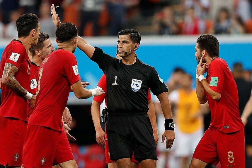 Paraguayan referee Enrique Caceres gesturing as he refers a penalty decision against Portugal to the VAR on Monday, amid the protests of the European champions' players.