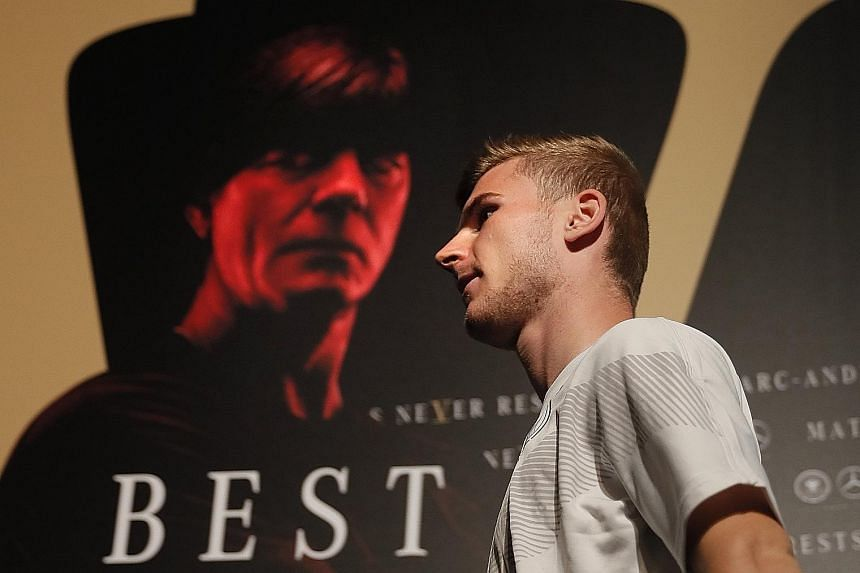 Forward Timo Werner leaving the podium after a Germany team press conference in Vatutinki, near Moscow, on Monday. The poster shows coach Joachim Low in Die Mannschaft's Mercedes-Benz World Cup campaign, which has the slogan Best Never Rest.