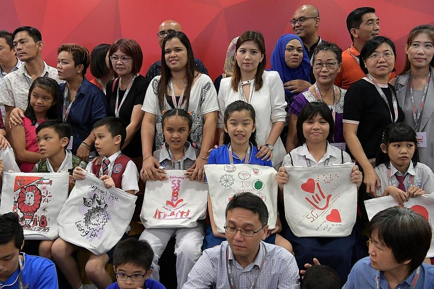 Above: Some of the young designers of this year's NDP funpacks displaying their creations at the launch event yesterday. The roughly 250,000 funpacks this year come in the form of tote bags to display the art clearly. Left: Funpack items include Sing