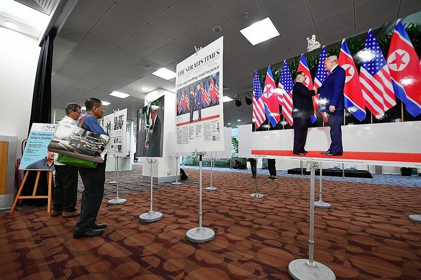 Visitors viewing photos of the Trump-Kim summit taken by ST executive photojournalist Kevin Lim at the National Library Building yesterday.