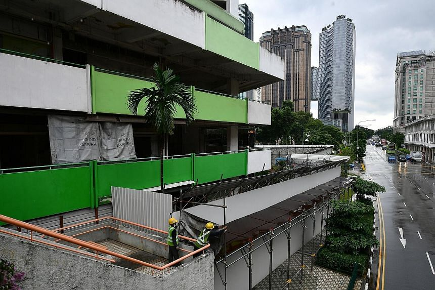 The demolition of the multicoloured Rochor Centre (above) began yesterday morning amid a rainstorm. Sound barriers (below, left) have been put up and the blocks will be demolished floor by floor (below, right).