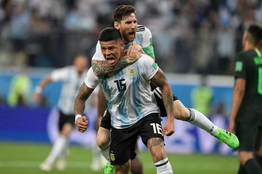 Argentina's defender Marcos Rojo (below) celebrates his goal with Argentina's forward Lionel Messi during the Russia 2018 World Cup Group D football match between Nigeria and Argentina at the Saint Petersburg Stadium in Saint Petersburg on June 26, 2