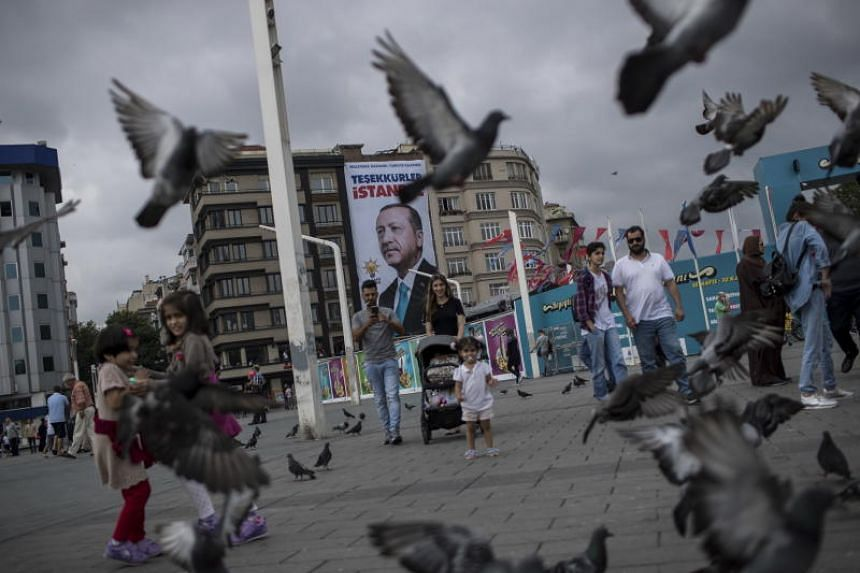 People walk in front of the poster of Turkish President Recep Tayyip Erdogan which reads, 'Thank you Istanbul' at Taksim Square in Istanbul, Turkey, on June 26, 2018.