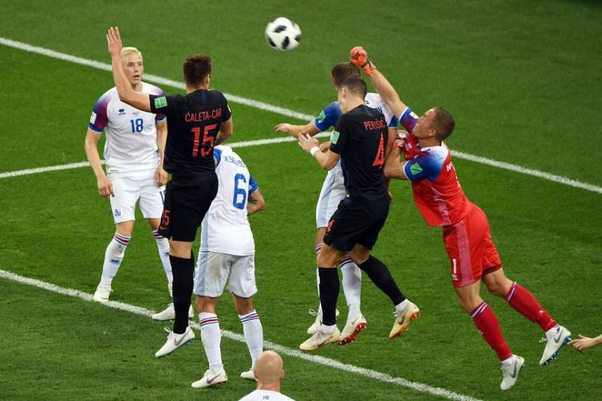 Iceland's goalkeeper Hannes Halldorsson (right) punches the ball away during the Russia 2018 World Cup Group D football match between Iceland and Croatia at the Rostov Arena in Rostov-On-Don on June 26, 2018.