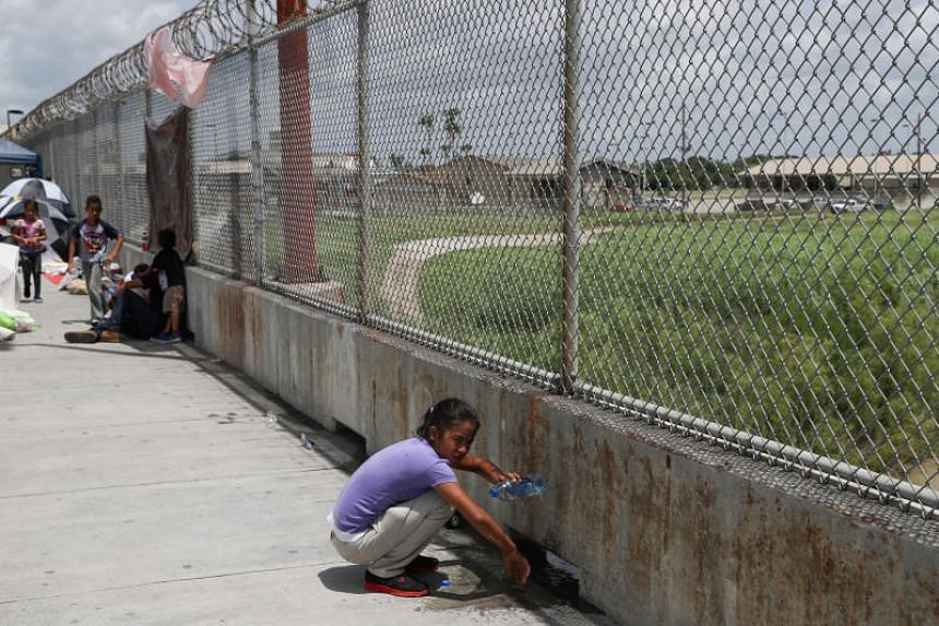 A Honduran girl bathes with a water bottle on the Mexican side of the Brownsville-Matamoros International Bridge after her asylum seeking family was denied entry by US Customs and Border Protection officers near Brownsville, Texas, on June 26, 2018.