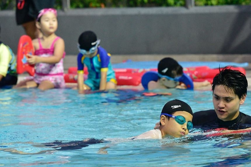 Joseph Schooling teaches Wong Wei Hong, 11, to swim at the launch of his swim school, Swim Schooling at Tampines Swimming complex on June 27,  2018.