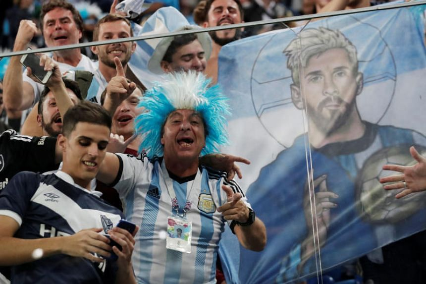 Argentina fans celebrate with a banner depicting Lionel Messi after the match.