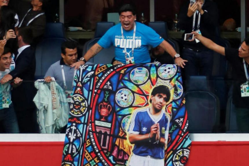 Fans take photos of Diego Maradona displaying a banner of himself in the stands before the match.