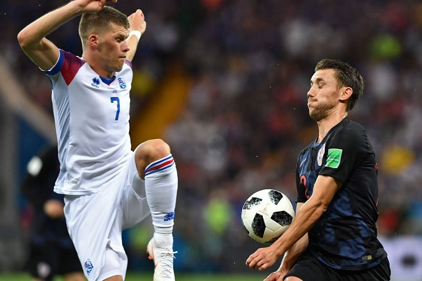 Iceland's midfielder Johann Gudmundsson (left) vies with Croatia's defender Josip Pivaric during the Russia 2018 World Cup Group D football match between Iceland and Croatia at the Rostov Arena in Rostov-On-Don, on June 26, 2018.