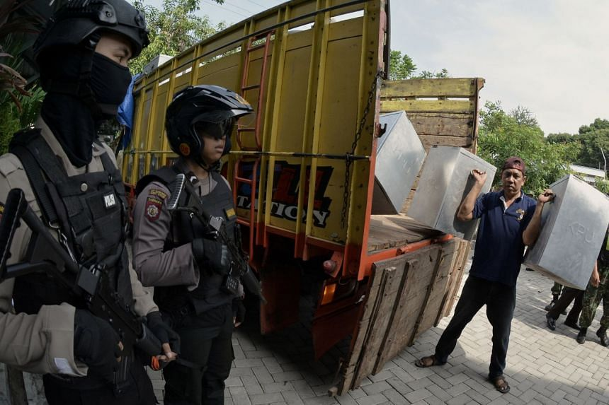 A worker carries ballot boxes and election material from a truck ahead of regional elections that are taking place this week across the archipelago nation in Madiun, East Java, Indonesia, on June 25, 2018.