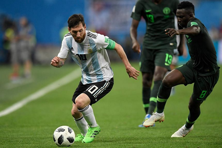 Argentina's Lionel Messi (left) competes for the ball during the Russia 2018 World Cup Group D football match between Nigeria and Argentina at the Saint Petersburg Stadium, on June 26, 2018.