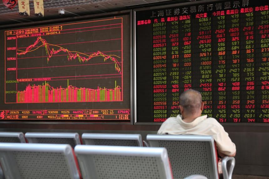 A Chinese investor watching an electronic board showing the stock index and prices at a securities brokerage house in Beijing, on June 26, 2018.