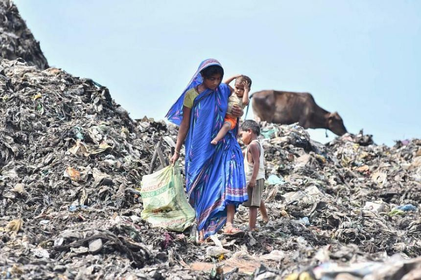 A woman collects firewood as she carries her child in the Boragaon area of Guwahati.