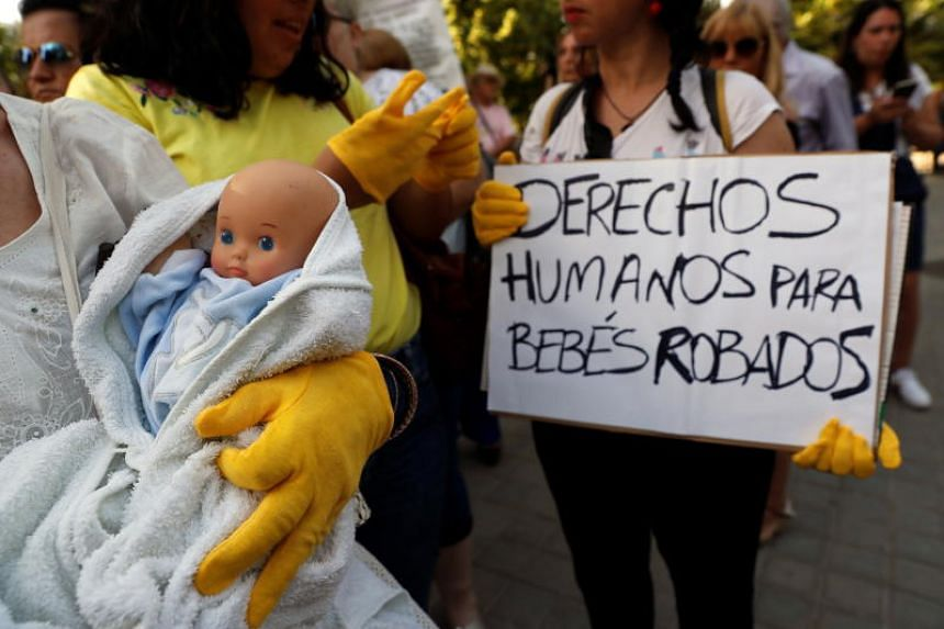 A protester holds a placard reading, 'Humans rights for stolen babies' as victims of the alleged snatched babies plot protest outside of the Provincial Court in Madrid, Spain, on June 26, 2018.