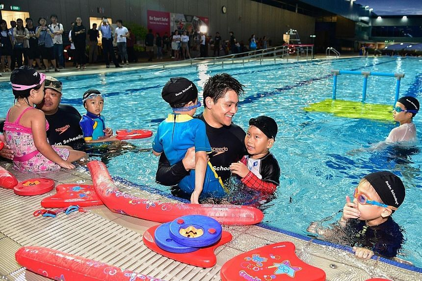 Joseph Schooling helping out a couple of trainees during the launch of his swim school, Swim Schooling, at Our Tampines Hub yesterday.
