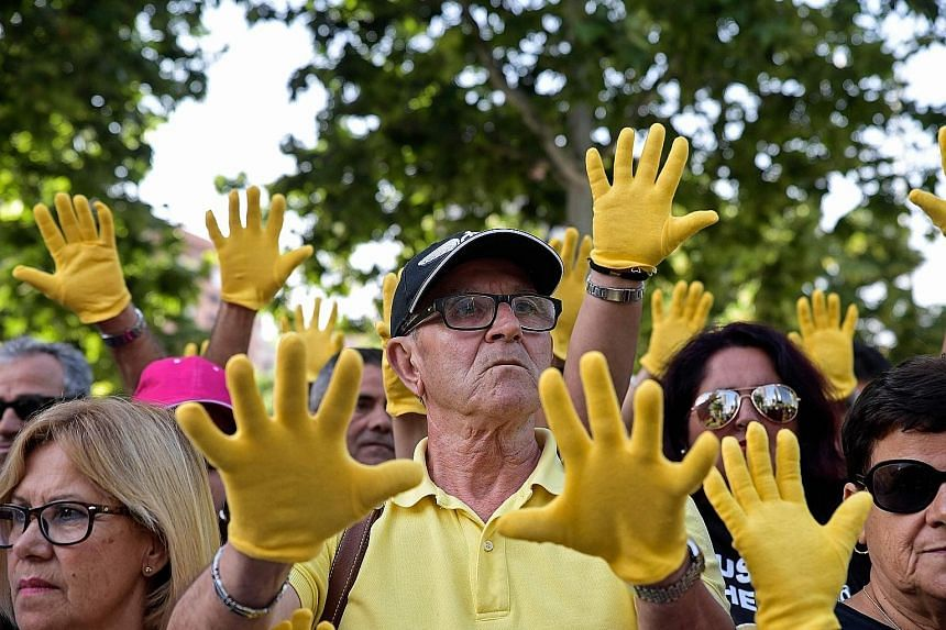 Demonstrators wearing yellow gloves, symbolising missing relatives, outside a provincial court in Madrid on Tuesday, the first day of the trial over thousands of suspected cases of babies stolen from their mothers during the Franco era.