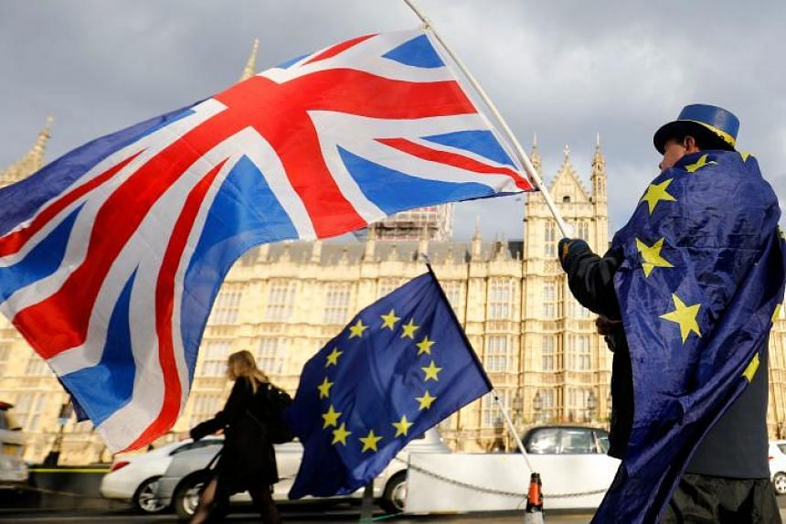 An anti-Brexit demonstrator waves a Union flag alongside a European Union flag outside the Houses of Parliament in London.