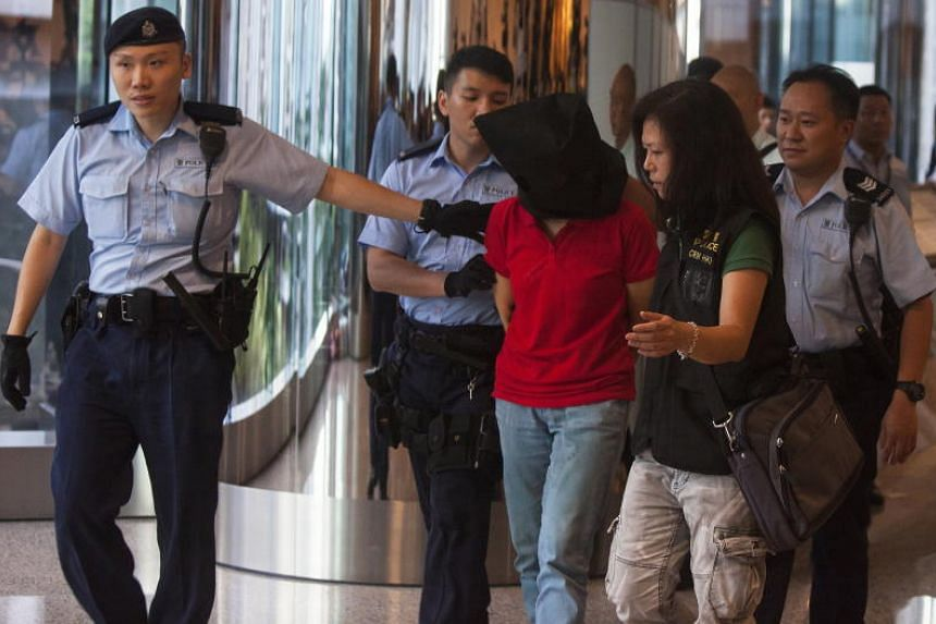 Hong Kong Police officers lead away a suspect (centre) arrested for a shooting that took place in Hong Kong's Quarry Bay Park on June 26, 2018.