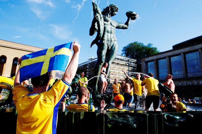 Swedish fans celebrate in a fountain at Gotaplatsen after Sweden won the match.