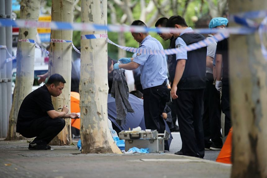 Police officers gathering evidence at the scene of a knife attack in front of a primary school in Shanghai's Xuhui district, on June 28, 2018.