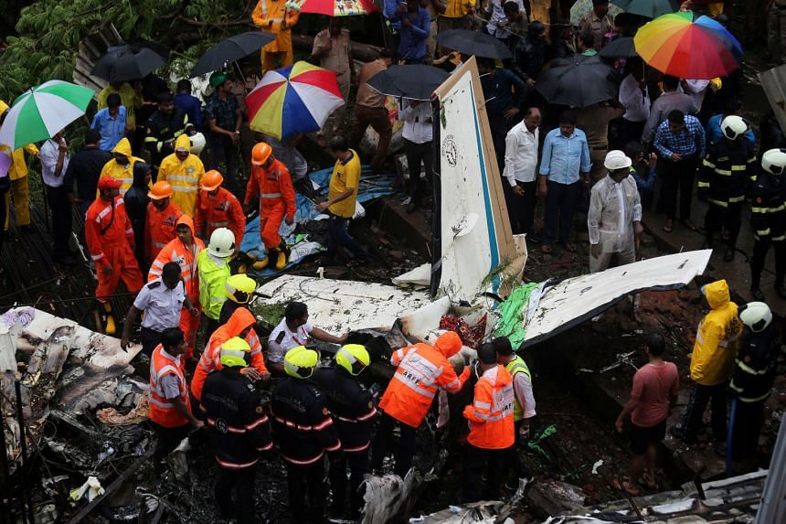 Firefighters and aircraft rescue workers inspecting the site of the plane crash in Mumbai on June 28, 2018.