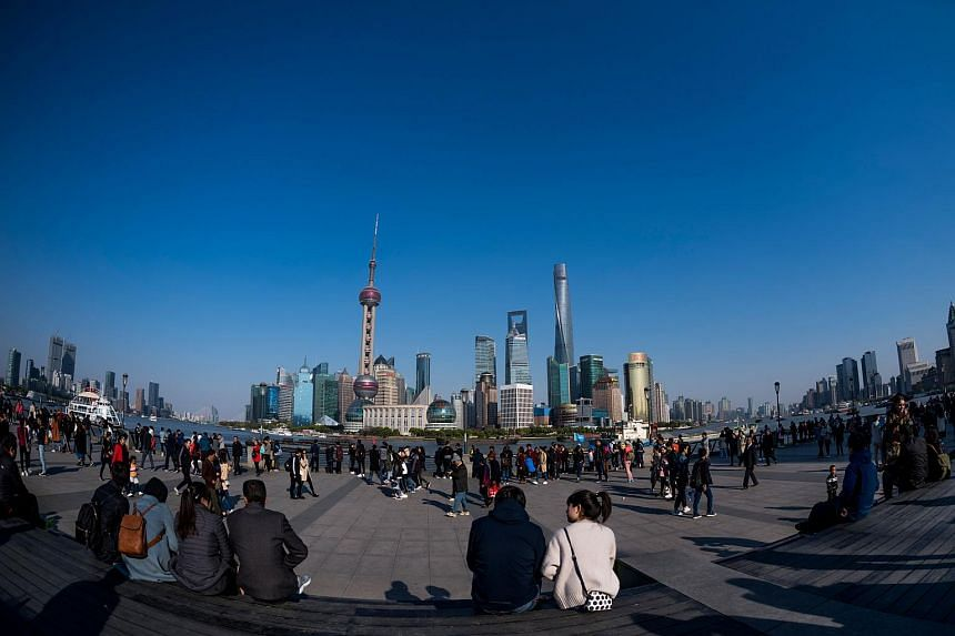 People enjoy the sun at the promenade on the Bund along the Huangpu River, near the financial district of Shanghai.