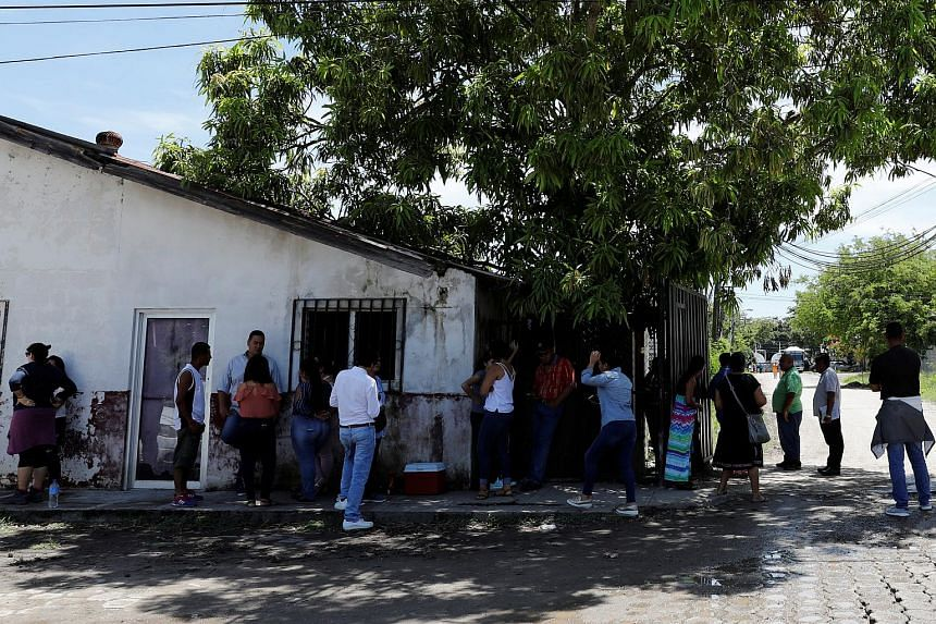 Families of the Honduras deportees from the US, under the Trump administration's hardline immigration policy, wait for relatives outside the a migrant centre in Honduras, on June 22, 2018.