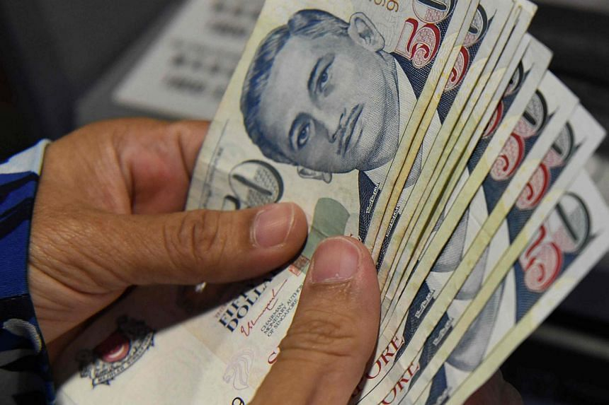 File photo showing Singapore dollar notes. The appointment of DP Info will facilitate the implementation of amendments to the Moneylenders Act earlier this year.