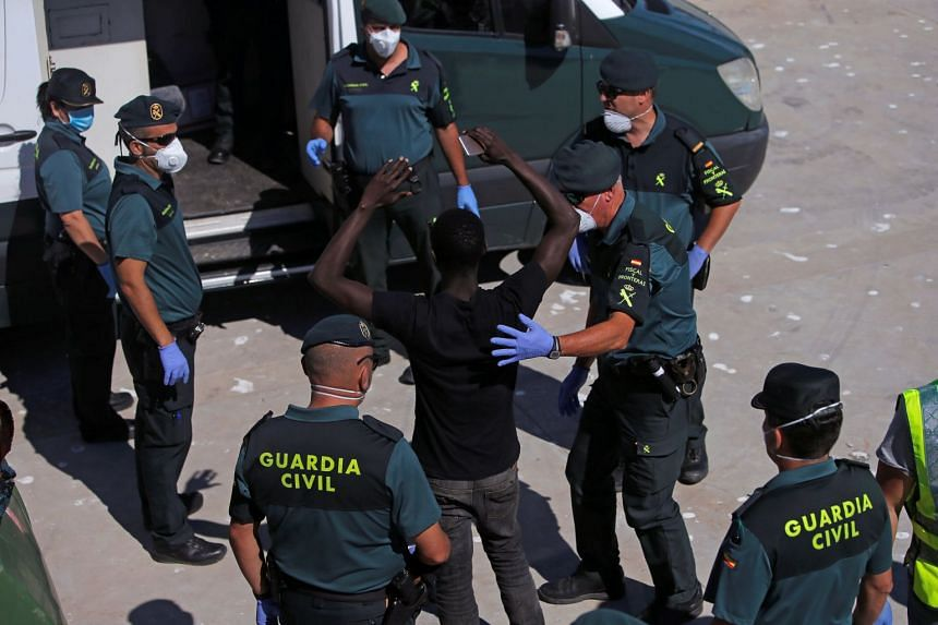 A migrant of a group intercepted aboard dinghies off the coast in the Strait of Gibraltar, is led by Spanish civil guards into a van at the port of Barbate, southern Spain, on June 27, 2018.