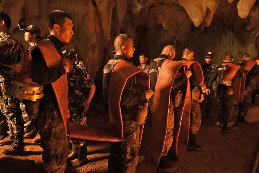 Thai soldiers carrying a hose deep into the Tham Luang cave complex in Chiang Rai yesterday. Rescuers have been pumping flood water from the cave where 12 schoolboys and their football coach are believed to be trapped.