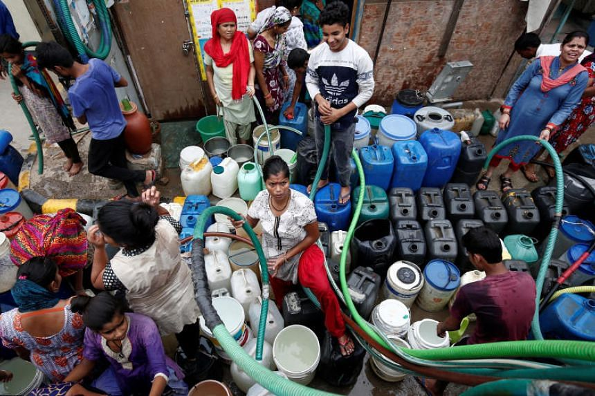 Residents fill their containers with drinking water from a municipal tanker in New Delhi on June 26, 2018.
