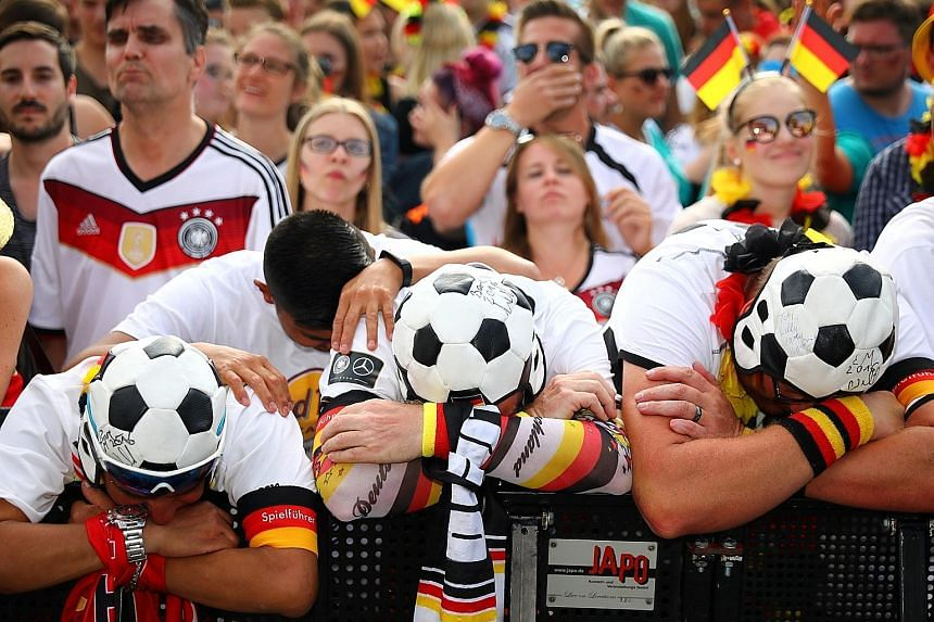 Upset German soccer fans at a public-viewing area at Berlin's Brandenburg Gate as their team lost 0-2 to South Korea on Wednesday. It was the first time since 1938 that Germany has crashed out of the World Cup in the first round.