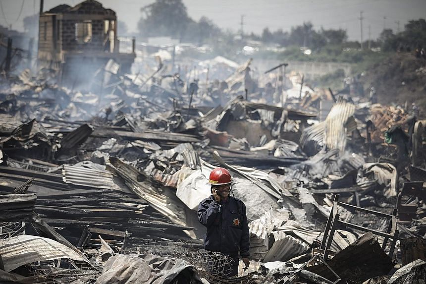 A rescue worker standing among the charred ruins after a huge fire destroyed timber shops in Gikomba market in Nairobi, Kenya, yesterday. The blaze broke out early in the morning and quickly spread to adjacent buildings and shops, killing at least 15