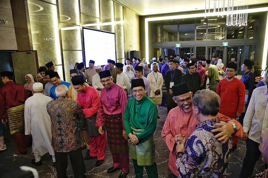 Minister-in-charge of Muslim Affairs Masagos Zulkifli (far right) and fellow ministers welcoming guests during yesterday's Hari Raya gathering at One Farrer Hotel and Spa - the first he was hosting as minister for the Malay/Muslim community.