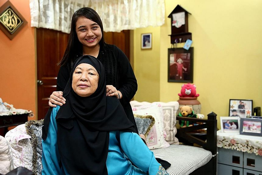 """Madam Sulami Hassan, who suffered a stroke two years ago, and her daughter Noor Sheela Sani at their flat in Yishun. The GST vouchers will """"help to lighten our financial burden"""", said Ms Noor Sheela, who also intends to use the Medisave top-ups to of"""