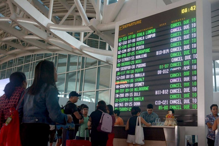 Travellers check their flights at Ngurah Rai airport in Denpasar, Bali which is closed on June 29, 2018.