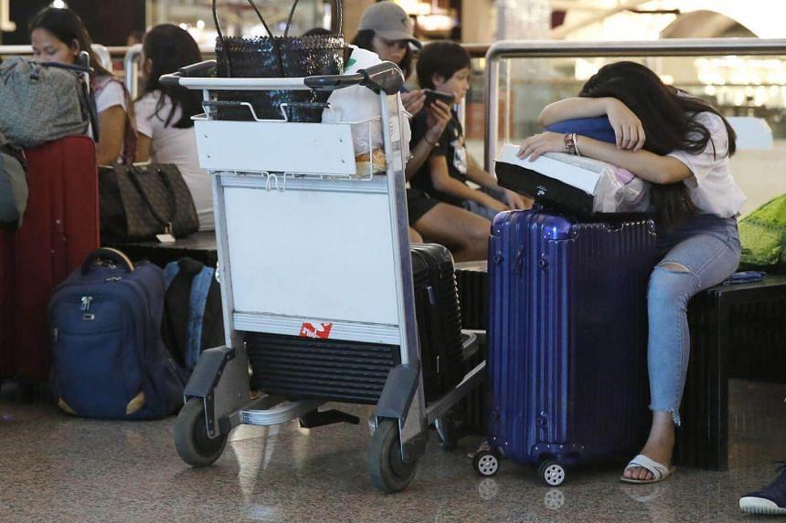 Passengers wait at Ngurah Rai airport in Denpasar, Bali following flight cancellations on June 28, 2018.