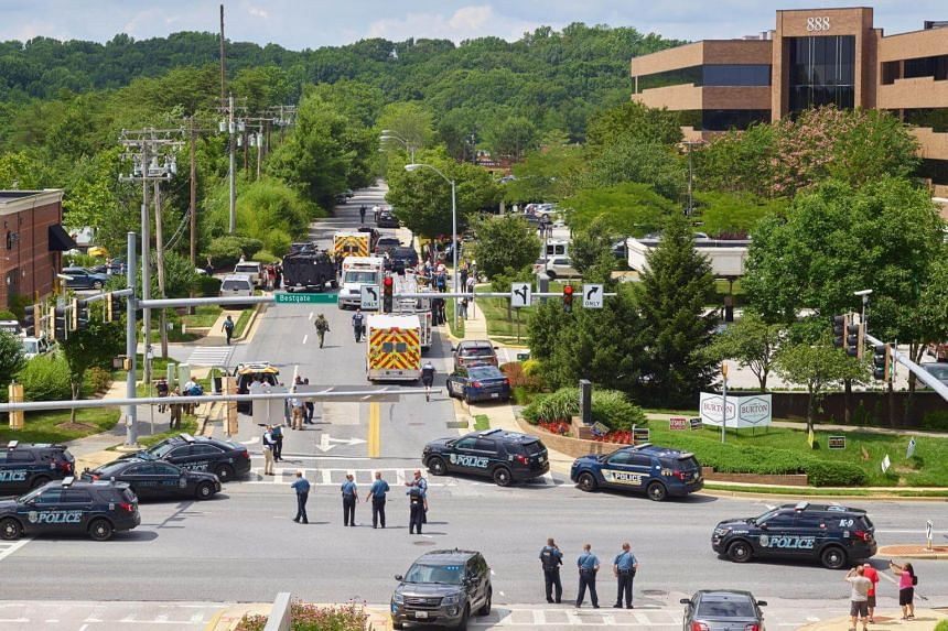 Police and first responders are seen outside the scene of a shooting at the Capital Gazette building in Annapolis, Maryland, on June 28, 2018.