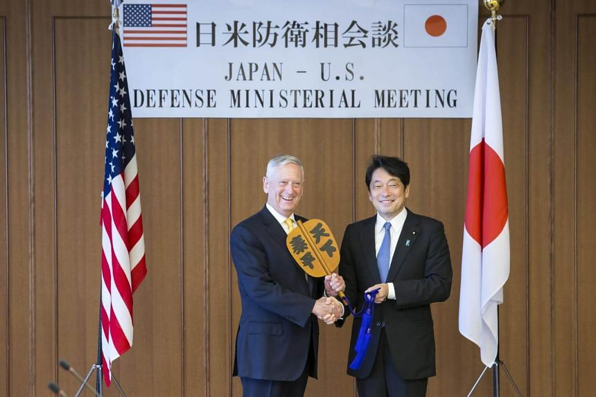 US secretary of defense James Mattis (left) and Itsunori Onodera, Japan's defense minister, hold a Gunbai war fan ahead of their meeting at the Ministry of Defense in Tokyo, Japan on June 29, 2018.