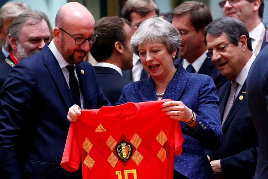 Britain's Prime Minister Theresa May receives Belgium's national soccer team jersey from Belgian Prime Minister Charles Michel as they attend an European Union leaders summit in Brussels, Belgium on June 28, 2018.