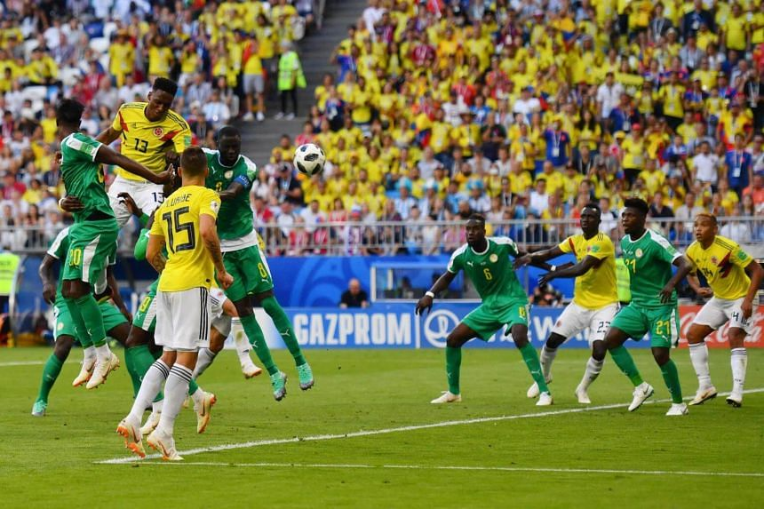 Colombia's defender Yerry Mina (centre) heads and scores a goal during the Russia 2018 World Cup Group H football match between Senegal and Colombia on June 28, 2018.