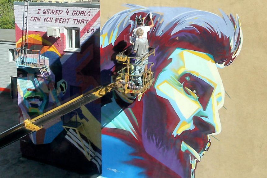A mural of Argentina's Lionel Messi is painted next to a mural of Portugal's Cristiano Ronaldo.