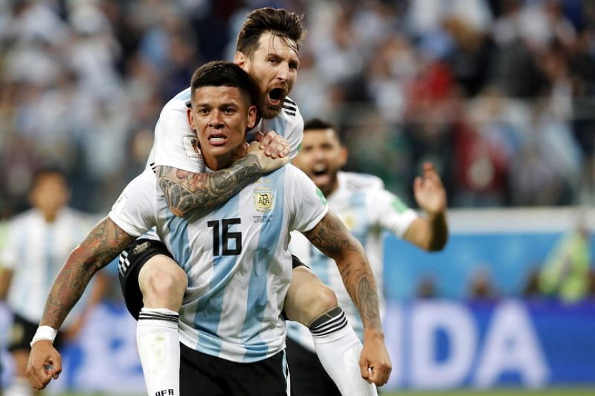 Marcos Rojo of Argentina celebrates with teammate Lionel Messi after scoring the winning goal against Nigeria.
