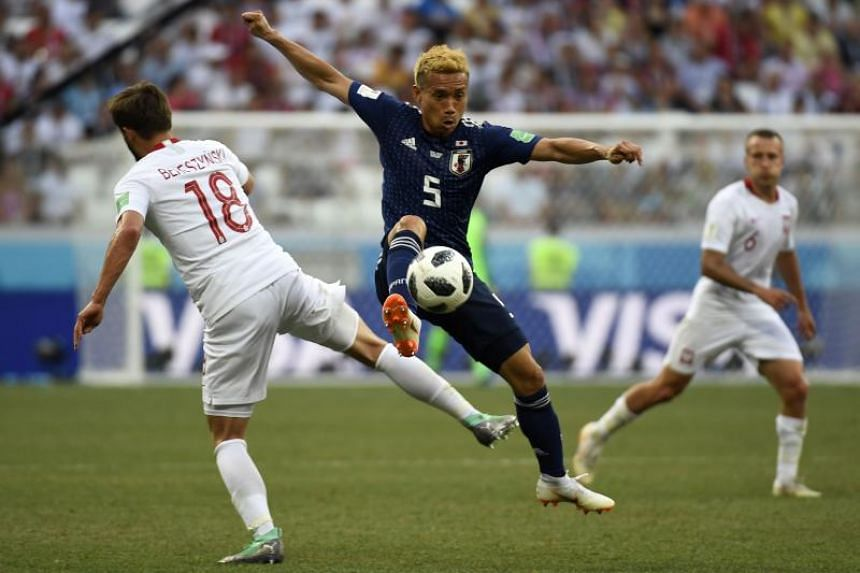 Japan's defender Yuto Nagatomo (centre) controls the ball during the Russia 2018 World Cup Group H football match between Japan and Poland at the Volgograd Arena in Volgograd on June 28, 2018.
