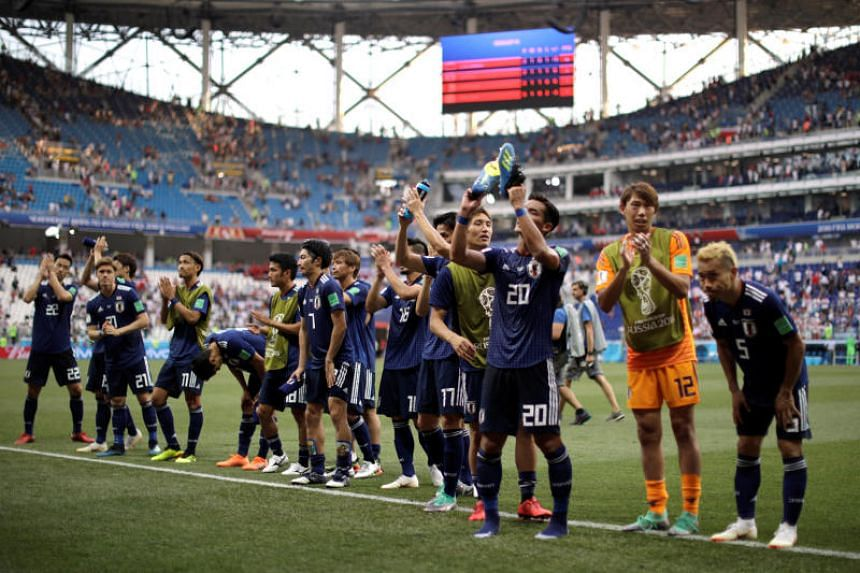 Japan players applaud their fans after the match as they qualified for the second round on June 28, 2018.